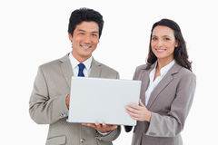 Smiling salesteam with laptop Stock Photography
