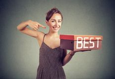 Smiling saleswoman advertising best product. Smiling young sales woman advertising best product holding a box stock images