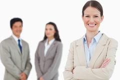 Smiling saleswoman with arms folded and associates behind her Stock Image