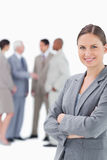 Smiling saleswoman with arms folded and colleagues behind her Royalty Free Stock Images