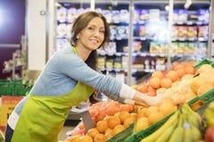 Smiling Saleswoman Arranging Oranges In Supermarket. Portrait of smiling saleswoman arranging oranges in supermarket stock photography