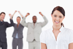 Smiling saleswoman with celebrating colleagues behind her Stock Photo