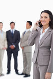 Smiling saleswoman on cellphone with team behind her Royalty Free Stock Images