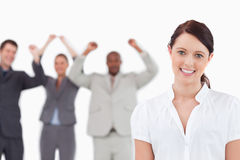 Smiling saleswoman with cheering associates Royalty Free Stock Image