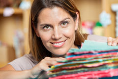 Smiling Saleswoman With Colorful Papers In Shop Royalty Free Stock Image