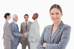 Smiling saleswoman with folded arms and colleagues behind her Stock Images