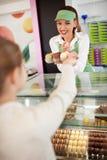 Smiling saleswoman gives macarons to young customer Stock Photo