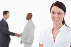 Smiling saleswoman with hand shaking colleagues behind her Stock Photos