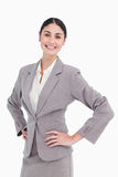 Smiling saleswoman with hands on her hip. Against a white background Royalty Free Stock Photo
