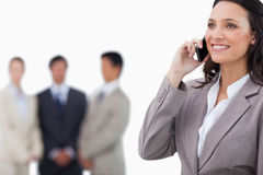 Smiling saleswoman on her mobile phone with team behind her Stock Image