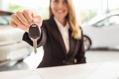 Smiling saleswoman holding car key Royalty Free Stock Photos