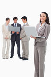 Smiling saleswoman with laptop and associates behind her Stock Images