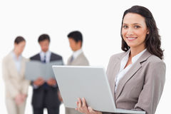 Smiling saleswoman with laptop and colleagues behind her Stock Photos