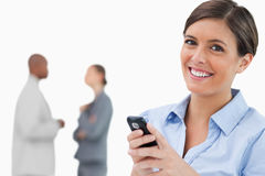 Smiling saleswoman with mobile phone and associates behind her Royalty Free Stock Images
