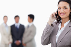 Smiling saleswoman on mobile phone with colleagues behind her Stock Photo