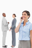 Smiling saleswoman on the phone with colleagues behind her Royalty Free Stock Photography