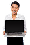 Smiling saleswoman presenting brand new laptop Royalty Free Stock Photo