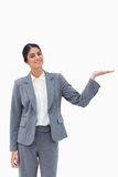 Smiling saleswoman presenting with her palm up Stock Photo