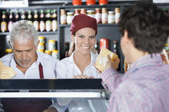 Smiling Saleswoman Serving Cheese To Customer In Shop. Portrait of smiling saleswoman serving cheese to customer while colleague working in shop Royalty Free Stock Image