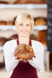 Smiling saleswoman showing bread in her hands Royalty Free Stock Photos