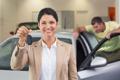 Smiling saleswoman showing a customer car key Stock Images