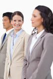 Smiling saleswoman standing between colleagues Stock Photography
