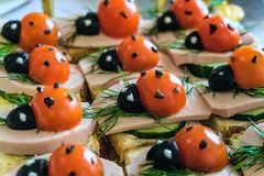 Smiling sandwiches with edible ladybugs from tomatos and olives, as well as bread, cheese, cucumber, sausage, dill. Perspective view with selective focus stock image