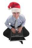 Smiling Santa. Businessman with santa's hat laughing over his work Royalty Free Stock Photos