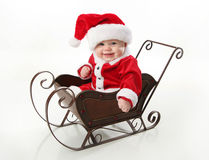 Smiling santa baby sitting in a sleigh. Adorable young baby wearing a santa claus suit and hat sitting in a metal Christmas snow sleigh Royalty Free Stock Photos