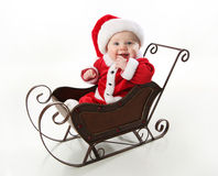 Smiling santa baby sitting in a sleigh. Adorable young baby wearing a santa claus suit and hat sitting in a metal Christmas snow sleigh Stock Photo