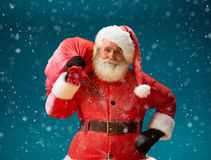 Smiling Santa Claus carrying big bag full of gifts to children on blue background. Royalty Free Stock Photography