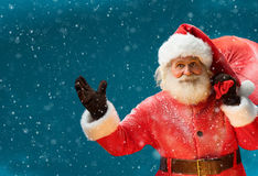 Smiling Santa Claus, carrying big bag full of gifts to children Royalty Free Stock Photos
