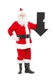 Smiling Santa Claus holding an arrow pointing down Stock Photos