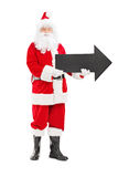 Smiling Santa Claus holding an arrow pointing right royalty free stock photo