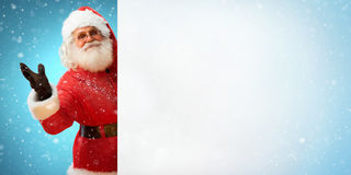 Smiling Santa Claus holding banner with  blank space for Your Text. Merry Christmas & New Year's Eve concept. Close up on blurred blue background Royalty Free Stock Image