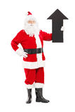 Smiling Santa Claus holding a big arrow pointing up Stock Photos
