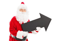 Smiling Santa Claus holding a big black arrow Stock Photos