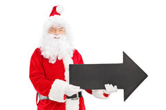 Smiling Santa Claus holding a big black arrow pointing right royalty free stock photography