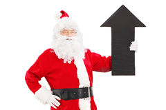 Smiling Santa Claus holding a big black arrow pointing up royalty free stock photo