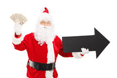 Smiling Santa Claus holding black arrow pointing right and dollars royalty free stock photography