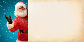 Smiling Santa Claus holding old paper banner with space for Your Text. Merry Christmas & New Year's Eve concept. Close up on blurred blue background Royalty Free Stock Photo