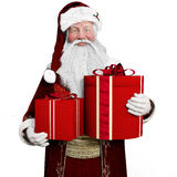 Smiling Santa Claus holding presents with a white background. Stock Images