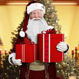 Smiling Santa Claus holding presents with a white background. Royalty Free Stock Images