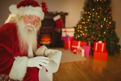 Smiling santa claus holding a scroll Royalty Free Stock Images