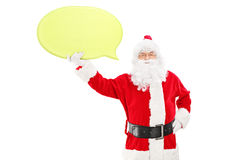 Smiling Santa Claus holding a speech bubble and looking at camer. Smiling Santa Claus holding an empty speech bubble and looking at camera isolated on white Royalty Free Stock Photos