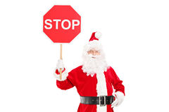 Smiling Santa Claus holding a stop sign Royalty Free Stock Image