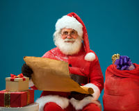 Smiling Santa Claus holding vintage roll and reads a long listof gifts for children. Royalty Free Stock Image