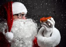 Smiling Santa Claus Is Holding Red Salmon Caviar Sandwich, Looking Glancing At Us Going To Eat Under The Snow. Stock Photos