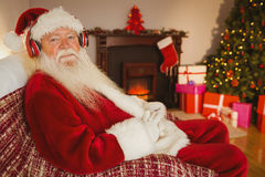 Smiling santa claus listening music Stock Photo