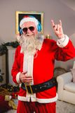 Santa claus listening to music on headphones at home. Smiling santa claus listening to music on headphones at home Stock Images